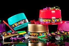 new years' eve party hats on  black background - stock photo