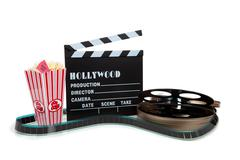 movie reel with clapboard and popcorn - stock photo