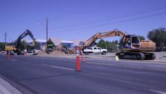 Excavators at road construcion working in heavy traffic, 1023  Stock Footage