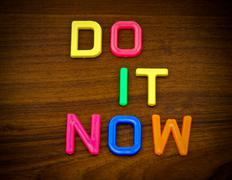 Do it now in colorful toy letters on wood background Stock Photos