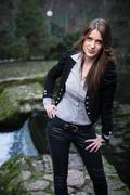 young woman in jacket standing and posing at the lake - stock photo