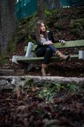 Young woman in jacket sitting at the bench Stock Photos
