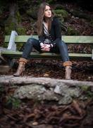 young woman in jacket sitting at the bench - stock photo