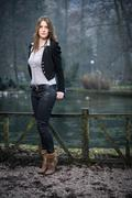 Stock Photo of young woman in jacket standing and posing at the lake