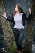 Stock Photo of young woman posing at the tree