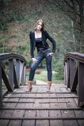 young woman standing at the bridge - stock photo