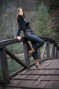 Young woman leaning at the bridge Stock Photos