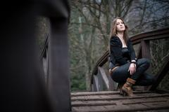 Stock Photo of young woman crouch at bridge