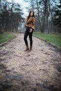 young woman in jacket standing and posing at the forest - stock photo