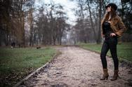 Stock Photo of young woman in jacket standing and posing at the forest