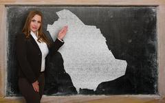 Teacher showing map of saudi arabia on blackboard Stock Photos