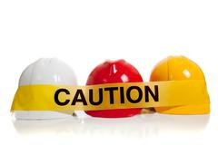various hard hats with caution tape - stock photo