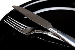 a fork and a knife on a black plate - stock photo