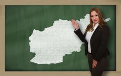 teacher showing map of afghanistan on blackboard - stock photo