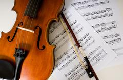 A violin and bow on sheet music Stock Photos
