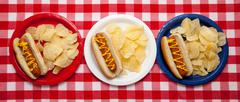 several hotdogs on colored plates - stock photo