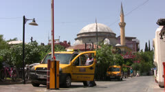 Taxis on a back street with mosque in background in Antalya Stock Footage