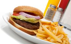 Hamburger and fries with ketchup and mustard, salt and pepper Stock Photos