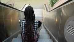 Dreadlock person sitting on moving escalator Stock Footage