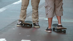 Two Skateboarders in the Middle of the Street Stock Footage