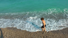 Boy throwing stones to the sea Stock Footage