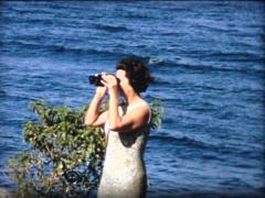 8MM 1960's woman spying with binoculars Stock Footage