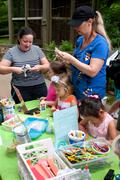 Parents help kids with arts and crafts project at festival Stock Photos