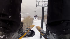 Riding a ski lift low shot between legs Stock Footage