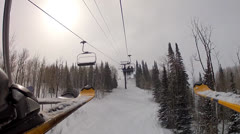 Riding a ski lift low shot by skis Stock Footage