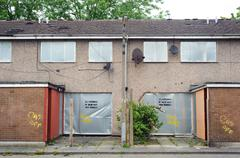 Abandoned terraced housing with metal shutters, Salford, UK Stock Photos