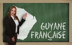teacher showing map of french guiana on blackboard - stock photo
