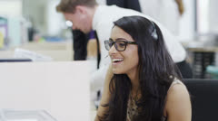Cheerful young customer service operator, at work in a busy call center - stock footage