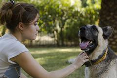 Young woman petting her dog Stock Photos