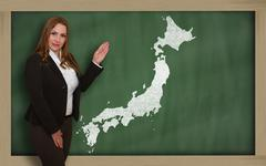 teacher showing map of japan on blackboard - stock photo