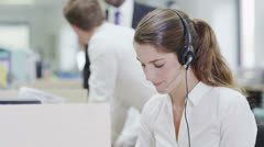 Stock Video Footage of Cheerful young customer service operator, at work in a busy call center