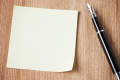 notepaper and black pen - stock photo