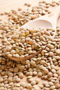 lentil on wooden spoon - stock photo