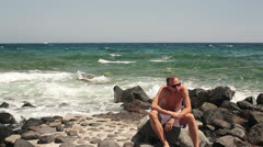 Sad, depressed man sitting on rocks by the sea HD Stock Footage