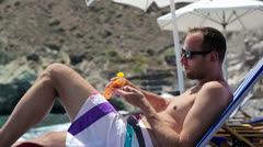 Man on sunbed applying sun block lotion on his arm HD Stock Footage