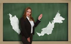 teacher showing map of malaysia on blackboard - stock photo