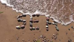Sea word written on sand with stone and waves. Sea summer concept Stock Footage