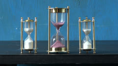 Three sand glass, hourglass on table and sand flow motion Stock Footage