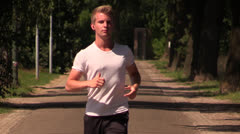 Slowmotion: Young attractive man jogging Stock Footage