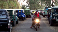 Traffic bikers at a line of parked SUVs. Bromo Tengger Semeru National Park Stock Footage