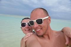 Happy young  couple at summer vacation have fun and relax at beach Stock Photos