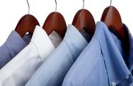 Stock Photo of blue dress shirts on wooden hangers