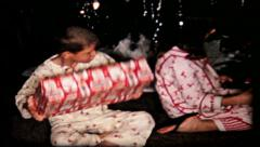 55 kids shaking Christmas presents under tree - vintage film home movie Stock Footage