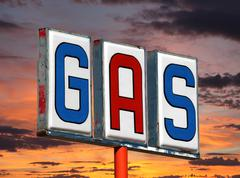 Old decayed gas sign with sunset sky Stock Photos