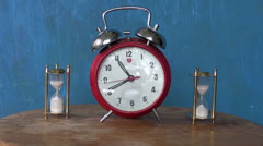 analog alarm-clock and two sand glass, hourglass on table. Time measure - stock footage