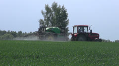 Agriculture tractor spraying summer  wheat field Stock Footage